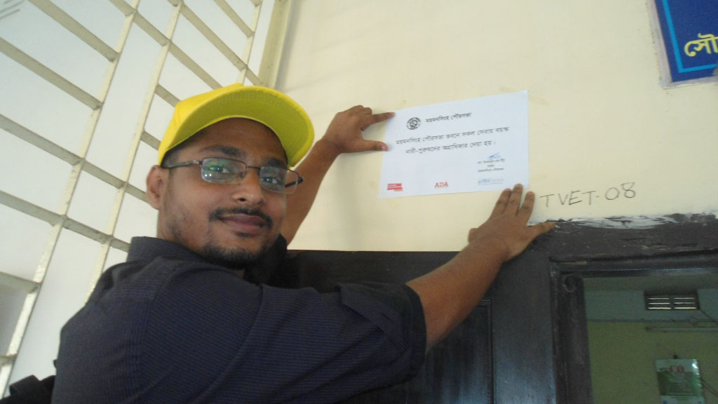 Mozammel Haque is attaching the signage at Mymensingh municipality.
